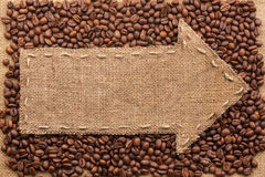 Pointer of burlap with place for your text, lying on a coffee be. Ans  background Royalty Free Stock Photos