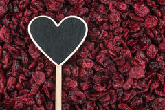 Pointer in the form of heart lies on dried cranberries Royalty Free Stock Photo
