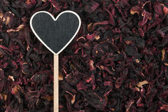 Pointer in the form of heart lies on dried hibiscus Stock Images