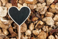 Pointer in the form of heart lies on dried mushrooms Royalty Free Stock Images