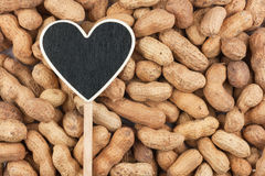 Pointer in the form of heart lies on peanut Stock Photography