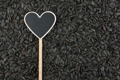 Pointer in the form of heart lies on sunflower seeds Stock Photos