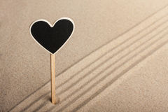 Pointer heart  standing in the sand Royalty Free Stock Photos
