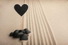 Pointer heart  standing  in the stones on the sand Stock Photo