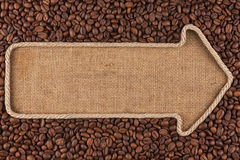 Pointer made from rope with  coffee beans  lying on sackcloth. With space for your text Royalty Free Stock Photo