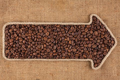 Pointer made from rope with  coffee beans  lying on sackcloth. With space for your text Stock Photo