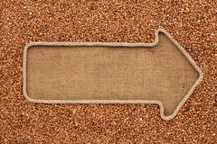Pointer made from rope with grain buckwheat  lying on sackcloth Royalty Free Stock Image