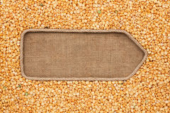 Pointer made from rope with grain peas  lying on sackcloth Stock Photos
