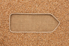 Pointer made from rope with grain wheat  lying on sackcloth Royalty Free Stock Photography