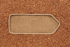 Pointer made from rope with grains buckwheat  lying on sackcloth Royalty Free Stock Image