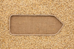 Pointer made from rope with grains oats lying on sackcloth Stock Photos