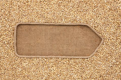 Pointer made from rope with grains pearl barley lying on sackcloth Stock Image