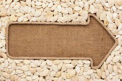 Pointer made from rope with  pumpkin seeds  lying on sackcloth Royalty Free Stock Image