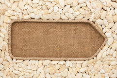 Pointer made from rope with pumpkin seeds  lying on sackcloth Stock Photo