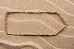 Pointer made of rope on the sand Stock Images