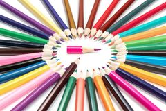 Pointer from pencils. Brown pencil indicates a short pink pencil in the middle of a circle of pencils isolated on a white background royalty free stock images