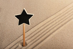 Pointer  star  standing in the sand Royalty Free Stock Image