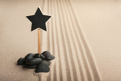 Pointer star standing  in the stones on the sand Royalty Free Stock Photography