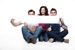 Pointind d'amis au panneau blanc Photographie stock
