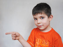Pointing. Young boy wearing orange t-shirt points his finger to the right Royalty Free Stock Images