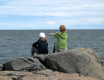Pointing. Girl and sitting boy by the ocean Royalty Free Stock Images