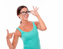 Pointing brunette woman with green tank top stock photos