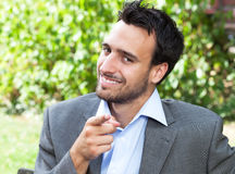 Pointing businesman in the park Royalty Free Stock Photos