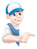 Pointing cartoon tradesman. Cartoon mechanic, plumber, handyman, decorator or gardener leaning around a sign and pointing Royalty Free Stock Photo