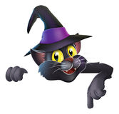 Pointing cartoon witchs cat. A happy cute Halloween black witchs cat wearing a witchs hat and pointing down at your banner or sign Royalty Free Stock Photography