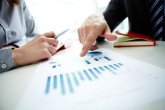 Pointing at chart. Image of male hand pointing at business document during discussion at meeting Royalty Free Stock Photo