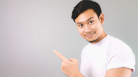 A pointing at content, empty copyspace. An asian man with white t-shirt and grey background stock photo