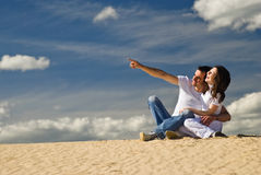 Pointing at distance. Young smiling couple sits on the dunes and man pointing at distance Stock Photography