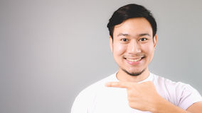 Pointing at the empty copyspace with smile happy face. An asian man with white t-shirt and grey background royalty free stock photo