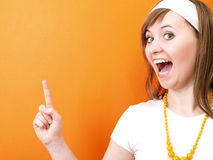 Pointing finger. Smiling girl on the orange background Stock Photos