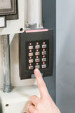 Pointing finger pressing the numeric keypad, Numpad. With red LED lights for staff get-in Stock Images