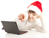 Pointing girl in Christmas hat with laptop Royalty Free Stock Photo