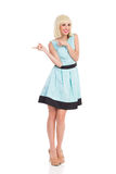 Pointing girl in light blue dress Stock Images
