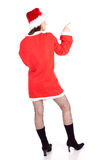 Pointing girl in red Santa clothes and hat Royalty Free Stock Image