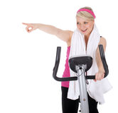 Pointing girl on stationary training bicycle Royalty Free Stock Photography