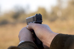 Pointing gun. Man holding a gun and taking aim Royalty Free Stock Images