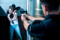 Pointing gun at kidnapper. Policeman is pointing gun at armed kidnapper Royalty Free Stock Photo