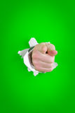 Pointing hand through hole Royalty Free Stock Photography