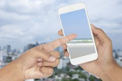 Pointing hand a picture of seascape in smartphone with buildings. Blur background Stock Photos