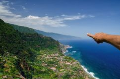 Pointing hand of sightseeing male tourist. Hand of male tourist pointing at view of north coast of Madeira island, Santana town surrounded by high mountains and Royalty Free Stock Photo