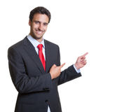 Pointing hispanic businessman with suit Stock Photos