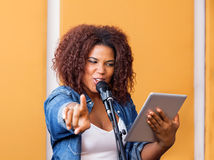 Pointing While Holding Digital för kvinnlig sångare minnestavla fotografering för bildbyråer