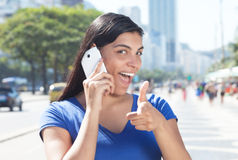 Pointing latin woman with long dark hair at phone in city Stock Images
