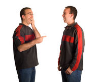 Pointing And Laughing. A man pointing and laughing at his identical twin, isolated against a white background Royalty Free Stock Photos