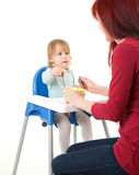 Pointing little boy feeding by his mother Stock Image