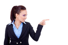 Pointing and looking to the side. Casual young business woman looking, pointing and smiling at copy space Royalty Free Stock Photo